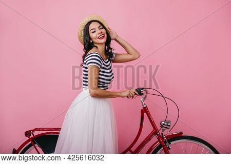 Tanned Blissful Lady In Hat Having Fun With Bicycle. Indoor Portrait Of Good-humoured Girl In Lush S