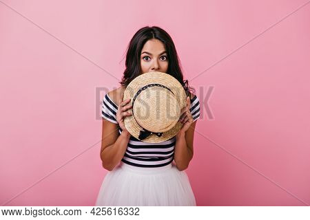 Graceful Tanned Woman Hiding Face Beside Straw Hat. Indoor Portrait Of Adorable Latin Lady Playfully