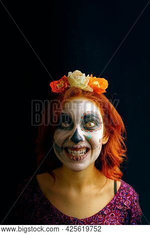 Young Woman In Day Of The Dead Mask Skull Face Art Makeup And Red Hair Showing Teeth On Dark Backgro
