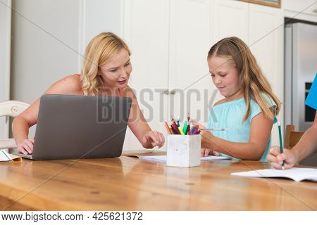 Caucasian mother using laptop and doing homework with her daughter smiling at home. family domestic life, spending time learning together at home.