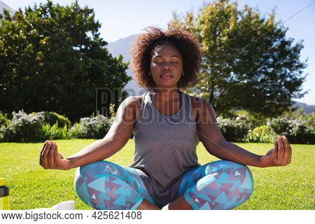 Midsection of african american woman practicing yoga with eyes closed in sunny garden. active lifestyle, outdoor fitness and leisure time.