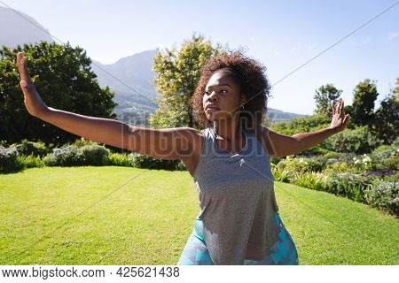 African american woman practicing yoga in sunny garden. active lifestyle, active lifestyle, outdoor fitness and leisure time.