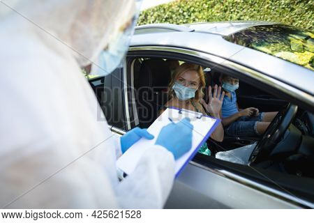 Medical worker wearing ppe suit taking notes with caucasian mother with son sitting in car. medical and health precautions, lifestyle during covid 19 pandemic.