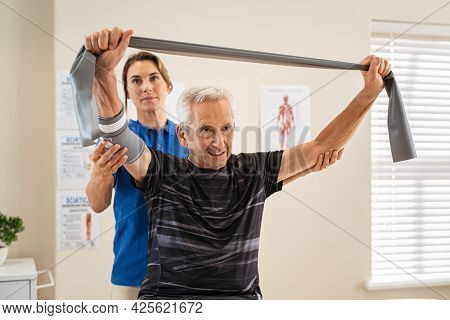 Young v working with senior patient in rehabilitation center. Trainer assisting senior patient in exercising with resistance band in private clinic. Rehabilitation physiotherapy worker working.