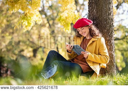 Beautiful young woman sitting on fallen autumn leaves in a park and reading a book. Happy smiling girl reading a book in park leaning on tree's trunk. Beautiful woman in autumn with a novel in hands.