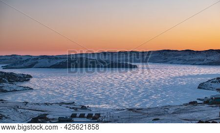 Dawn Over A Frozen Lake. The Sky Above The Ridge Is Colored Orange. Glare Of The Sun On The Surface