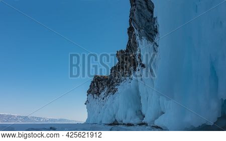A Granite Rock, Devoid Of Vegetation, Rises Above The Frozen Lake Baikal. The Base Is Covered With A
