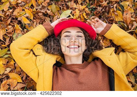Happy smiling woman lying over yellow leaves and looking at camera. Young beautiful woman lying on dry autumn leaves with a big grin. Portrait of cheerful girl rest on ground in park.