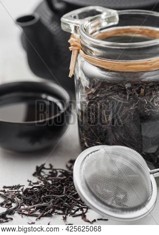 Glass Jar Of Black Loose Organic Tea With Teapot And Cup With Tea Strainer Infuser On Light Backgrou