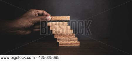 Close-up Hand Is Placing Wood Block Tower Stacked In Stair Step With Caution To Prevent Collapse Or
