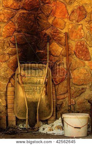 Carretilla vieja contra el muro de piedra