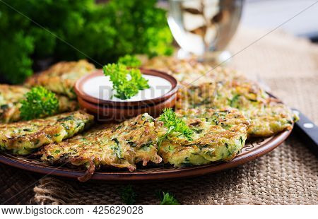 Zucchini Fritters. Vegetable Vegetarian Zucchini Pancakes With Sauce On Wooden Background. Healthy F