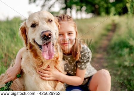 Portrait of beautiful preteen girl with golden retriever dog looking at camera together, hugging and smiling outdoors. Kid with doggy pet in the field in summer time