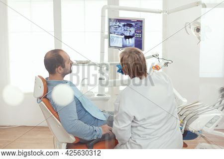 Stomatologist Discussing With Patient Sitting In Stomatological Chair In Dental Clinic. Senior Docto