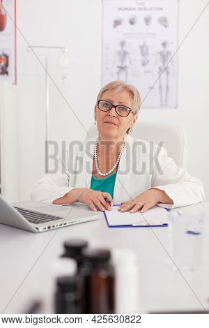 Portrait Of Practitioner Senior Woman Doctor Looking Into Camera Sitting At Desk In Conference Meeti