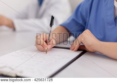 Close-up Of Physician Woman Nurse Hand Analyzing Sickness Examination Writing Medical Expertise On C
