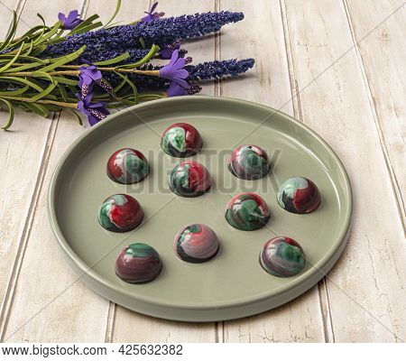 Collectible Handmade Tempered Chocolate Sweets With A Glossy Painted Body On A Round Plate. Stock Ph