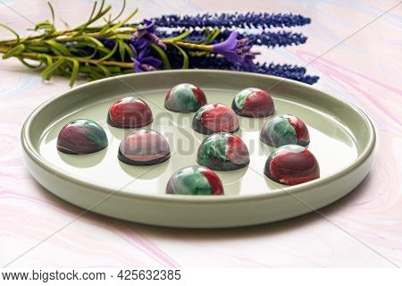 Collectible Handmade Tempered Chocolate Candies With A Glossy Painted Body On A Round Plate With A B