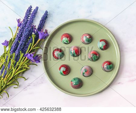 Collectible Handmade Tempered Chocolate Sweets With A Glossy Painted Body On A Round Plate With Blur