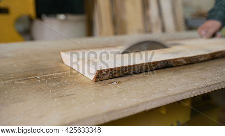 Cutting Wooden Board On A Table Saw. Woodworking And Carpentry. Furniture Manufacturing. A Craftsman