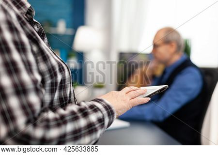 Close Up Of Senior Woman Hand Scrolling On Digital Device In Home. Close Up Of Elderly Woman Using M
