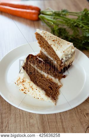 Two Slices Of Carrot Cake On A White Plate With Rustic Carrot On The Side