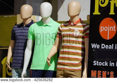 Full-length Three Male Mannequin Dressed In Casual Clothes (shirt And Trousers) Displayed Outside A