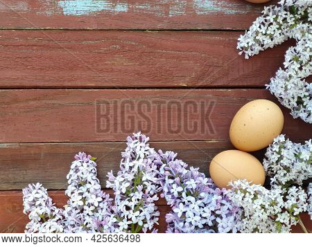 Two Brown Eggs Of Domestic Chickens And Lilac Flower On Old Red Wood Texture Background. Spring And