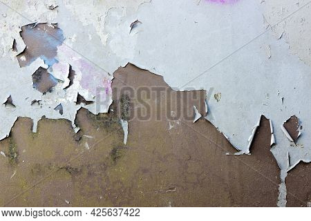 Large Sections Of Blue Paint Peel Off A Brown Metal Surface. The Paint Is Heavily Cracked And Weathe