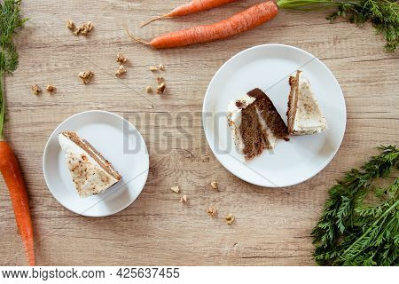 Piece Of Carrot Cake On A White Plate On A Wooden Table. Two Carrots And Walnuts For Decoration.