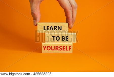 Learn To Be Yourself Symbol. Wooden Blocks With Words Learn To Be Yourself On Beautiful Orange Backg