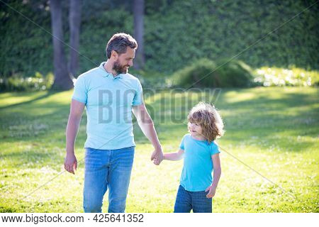 Happy Son And Father Holding Hands Walking On Sunny Summer Day In Park Grass, Fatherhood