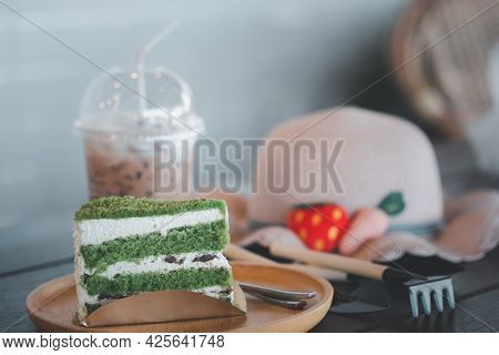 Close Up Of Slices Of Soft Spongy Layer Cake With Sweet Cream And Red Beans And Girl Hat