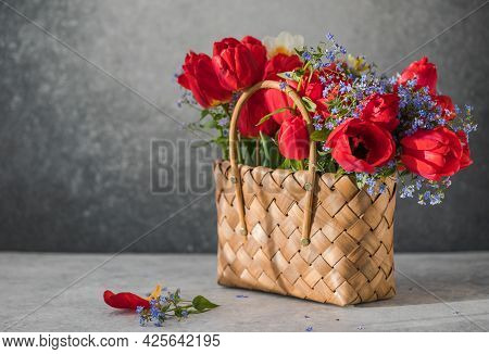 Summer Or Spring Bouquet Of Daffodils And Red Tulips  In A Wicker Basket Located On A White Backgrou