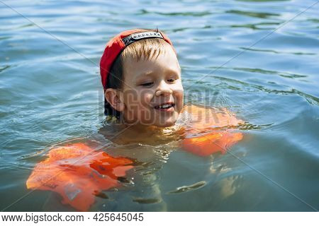 Child Active Recreation In Nature, Outdoors. Happy Little Boy In A Cap And Inflatable Life-saving Ar