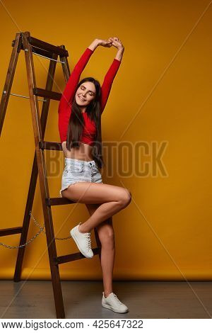 Young Female Model With A Perfect Slim Body And Dental Braces Posing On A Yellow Background. Young W