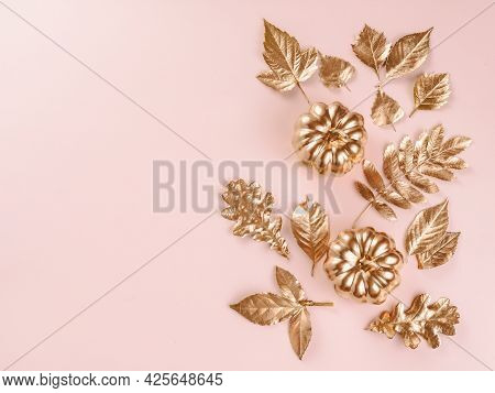 Gold Autumn Leaves On Pink Background. Autumn Concept. Top View Of Autumn Leaves In Gold Paint On Wh