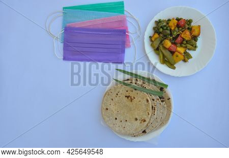 Overhead View Of Mix Veg Of Matar Paneer And Shimla Mirch Recipe With Chapati (roti) And Face Mask I