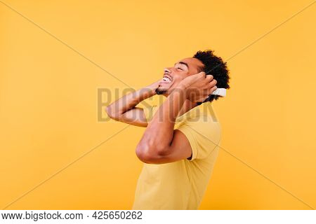 Good-humoured Young Man Listening Favorite Song With Eyes Closed. Excited Carefree African Guy Posin