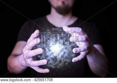 Energy Ball In Wizard Hand. Bearded Man Casting Bright Magic Ball Spell. Black Background