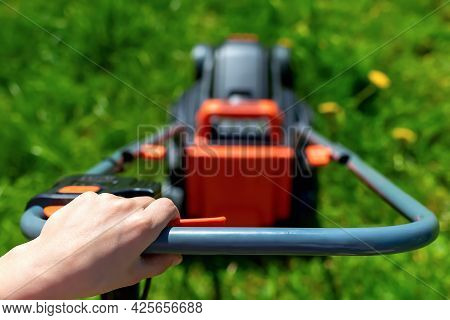 Close-up And Selective Focus Of Hand Of Young Woman Who Holds Handle Of Lawn Mower. Concept Of Summe