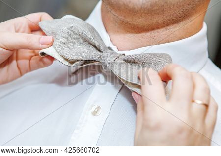 How To Tie A Bow Tie. The Woman Ties A Tie Around The Man's Neck. Close-up. Unrecognizable Person