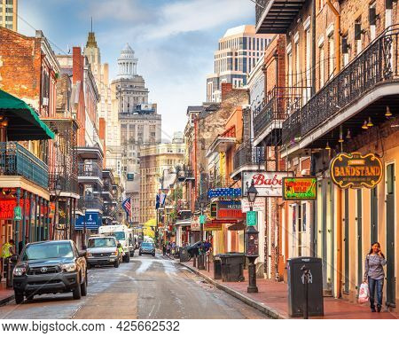 NEW ORLEANS, LOUISIANA - MAY 10, 2016: Traffic and pedestrians on Bourbon Street in the day. The historic street is the heart of the French Quarter.