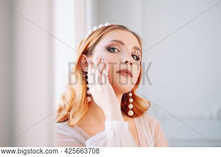 Close-up Portrait Of A Pretty Red-haired Woman With Makeup Made Of Pearls On Her Hand And Face, A Pe