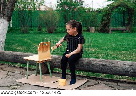 A Full-length Enthusiastic Girl Paints A Small Chair In The Garden On A Green Lawn With Yellow Paint