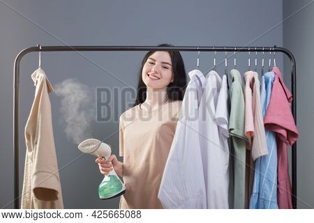 Young Brunette Girl With Steamer And Clothes