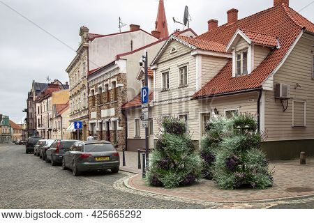 Latvia, Cesis, August, 2020 - Old Restored Wooden Houses Under Red Roof Tiles In The Narrow Streets