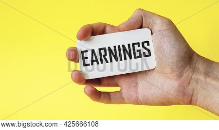 Hand Holds A Card With The Word Earnings On A Yellow Background