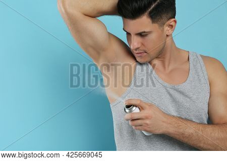 Handsome Man Applying Deodorant To Armpit On Turquoise Background, Space For Text