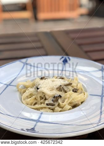 Homemade Pasta With Mushroom Truffles In A Creamy Sauce Sprinkled With Parmesan Cheese